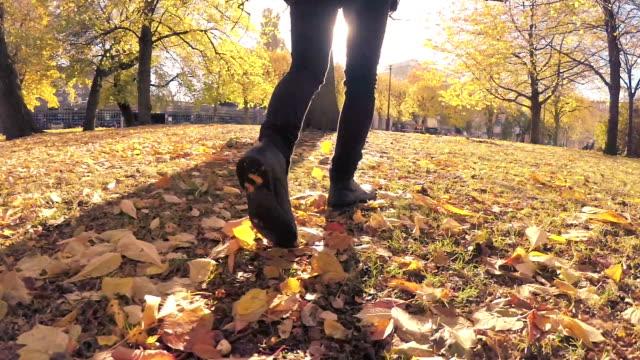 Man Walking through Autumn Leaves