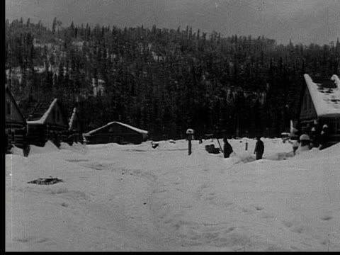 1927 B/W WS MS PAN MONTAGE Man walking through village in snow drift, portrait of group of people standing outside log cabin, Ontario, Canada