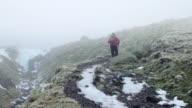 WS man walking through winter mountain landscape