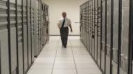 SLO MO WS Man walking toward camera in corridor, stopping and smiling, Dallas, Texas, USA