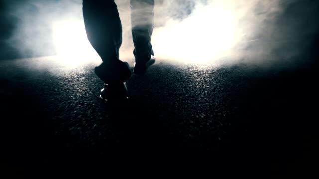 Man walking towards light at night