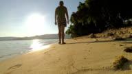 Man walking towards the sun on a beach