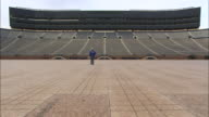 A man walks across the bare football field at the University of Michigan.