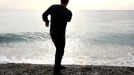 Mann zu Fuß auf einer einsamen Strand, Meer, Sprünge rock