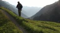 Man walks along track above mountain ranges, sunrise