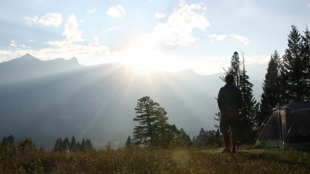 Man walks by tent to view sunset, from mountain meadow