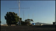 (HD1080) Man Walks Dog In Front Of Mast And Volcano