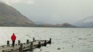 Man walks down to lake-shore after a rain storm