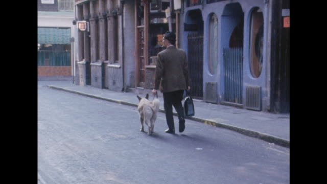 A man walks his dog along a street in London's Soho district