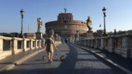 A man walks his dog on the bridge crossing the Tiber River towards the Castel Sant Angelo, Rome