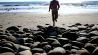 Man walks on shoreline rocks