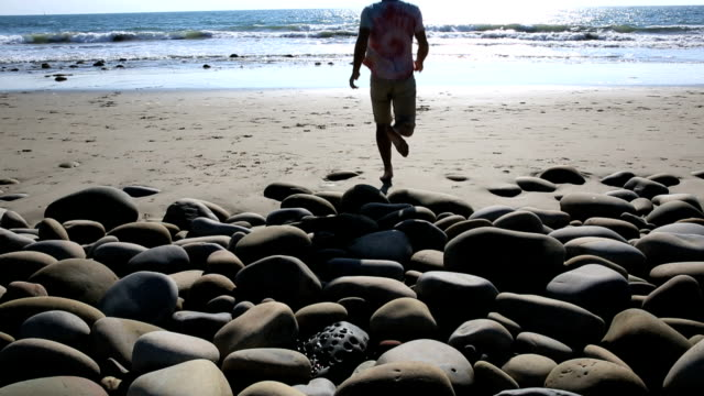 Man walks on shoreline rocks