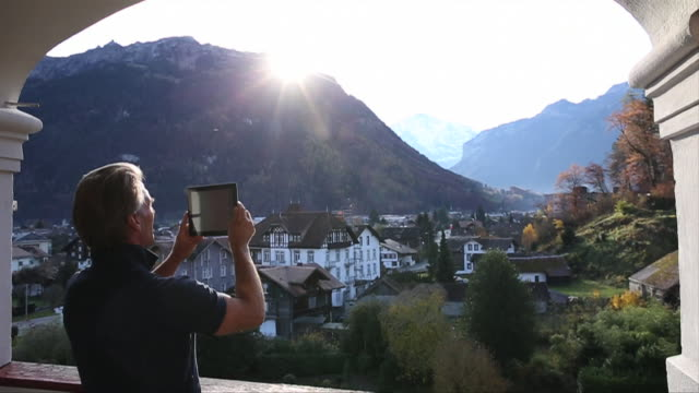 Man walks onto terrace, takes digital tablet pic of view