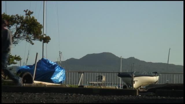 (HD1080) Man Walks Past Dry-docked Boats
