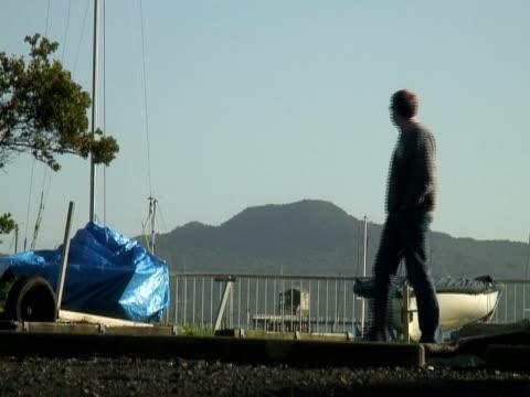 Man Walks Past Dry-docked Boats