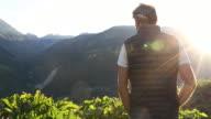 Man walks through mountain meadow at sunrise