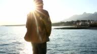 Man walks to sea edge, looks off, sunrise