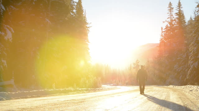 Man walks up winter road into the sun