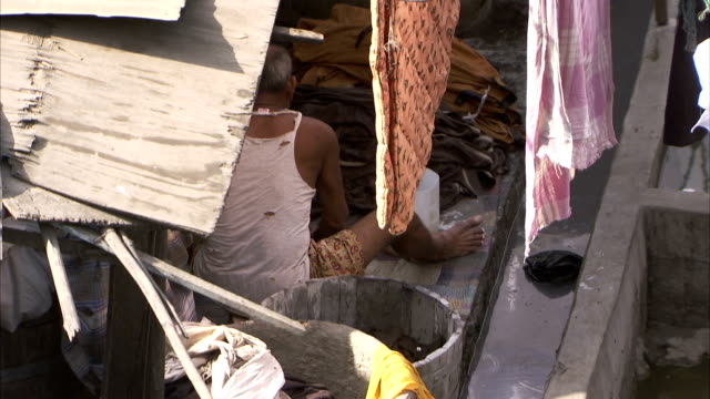 A man washes clothing with a bucket and brush inside a house. Available in HD.