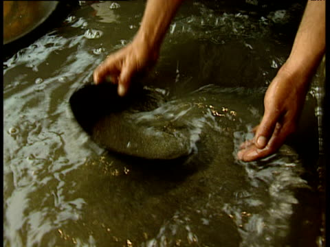 Man washes mud to separate gold residue in bottom of pan Alta Floresta Brazil 1993