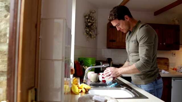 Man washing dishes in his home