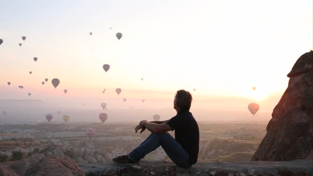 Man watches balloons rise above desert landscape