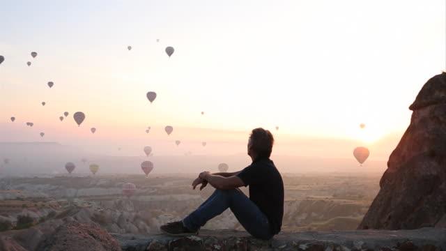 Man watches balloons rise above desert landscape