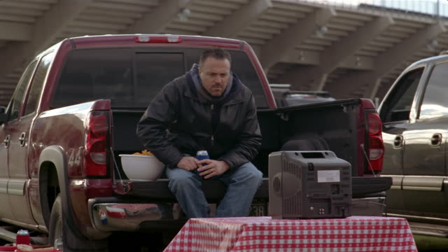 Man watching football game on television set at tailgate party in parking lot of stadium / man coming over and joining him