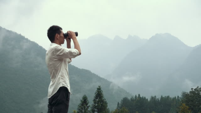 Man watching mountains through binoculars