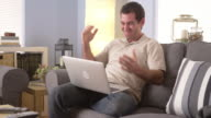 Man watching the game on his laptop