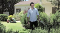 MS Man watering lawn and wife and child playing on lawn in the background / Santa Monica, CA, United States