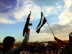 A man waves the Syrian Republic flag while another holds a gun