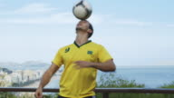 MS A man wearing a Brazil t-shirt practices his football skills with Rio in the background / Rio de Janeiro, Brazil