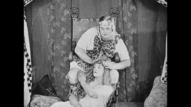 Fatty Arbuckle, wearing a leopard skin, strokes a female impersonating Buster Keaton's head, and Keaton plucks hair from Arbuckle's knee causing him discomfort