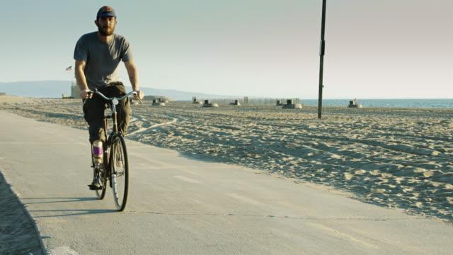 Man Wearing Artificial Leg Riding Bike on Beach