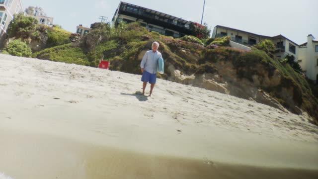 MS LA Man wearing business shirt running into water with surfboard, Laguna Beach, California, USA
