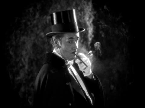 1925 CU B/W Man wearing cape and top hat smoking cigarette in garden at night
