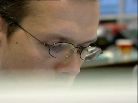 Man wearing glasses concentrates as he looks downwards towards computer in office