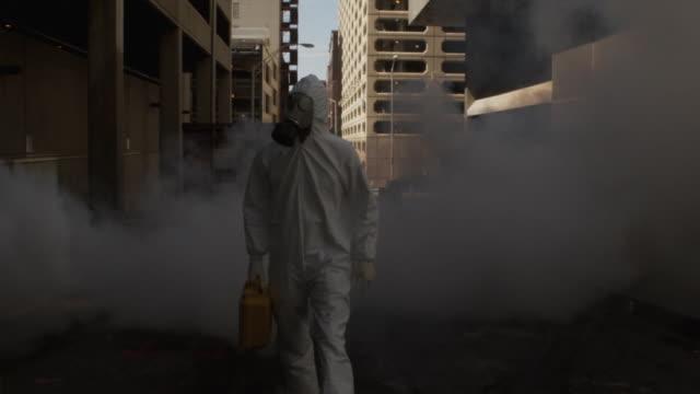 SLO MO MS TU REAR POV Man wearing HAZMAT suit and gas mask, carrying case in smoke, Atlanta, Georgia, USA