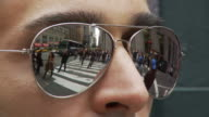T/L ECU Man wearing mirror shades reflecting busy street / New York City, New York, USA
