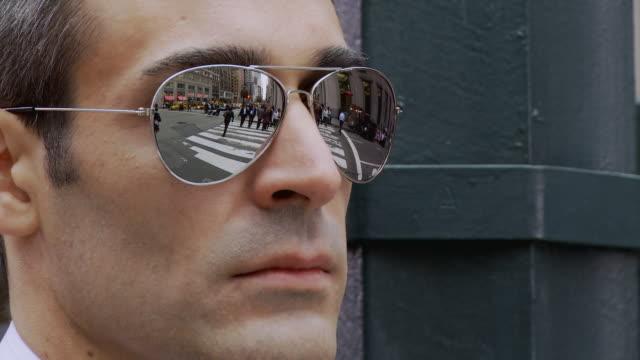 ECU Man wearing mirror shades reflecting busy street / New York City, New York, USA
