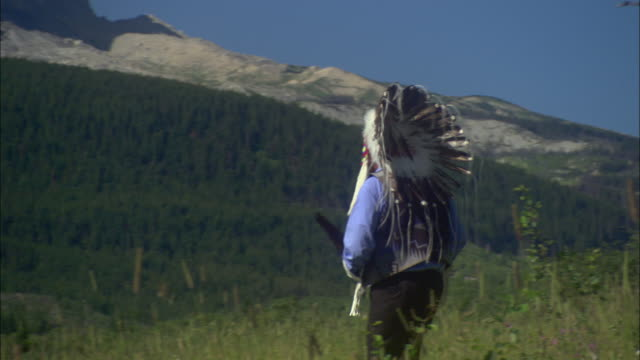 MS ZO WS Man wearing native American war bonnet and traditional vest and carrying feather walking on meadow, facing mountain / Glacier National Park, Montana, USA