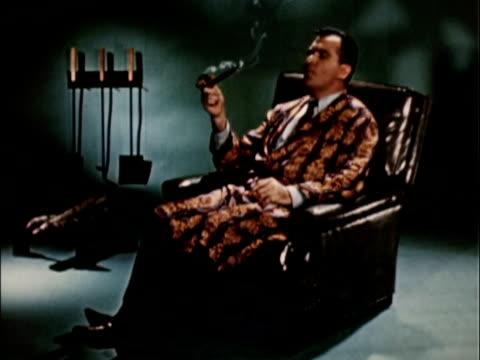 1956 WS Man wearing smoking jacket on leather recliner / USA