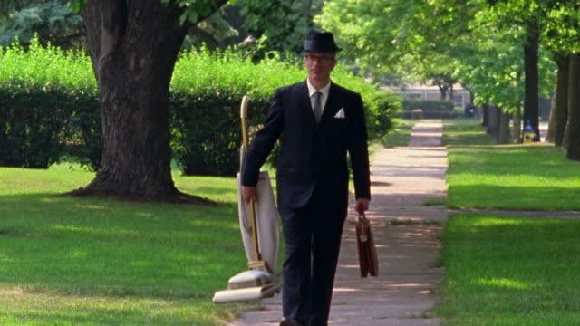 REENACTMENT Man wearing suit walks down sidewalk and carrying briefcase + vacuum cleaner