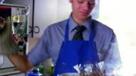 MS man wearing tie + apron shaking head + looking upset at smoking burnt rack of lamb