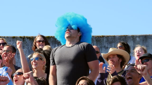 MS Man wearing wig at soccer match standing with arms raised leading crowd in cheering