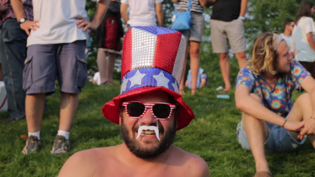 A man wears red and white striped sunglasses an Uncle Sam top red white and blue sequin top hat and white plastic mustache while hundreds of Grateful...