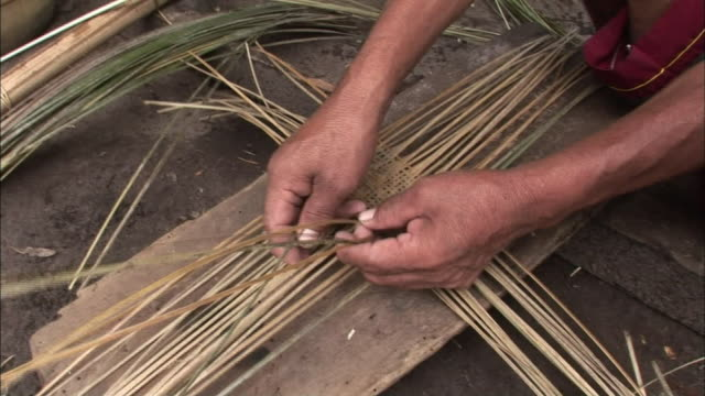 A man weaves plant fibers to make a basket.