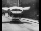 Man wheels trailer with early attempt at airplane out of building / machine with flapping wings rolls away along street / man sits on large...