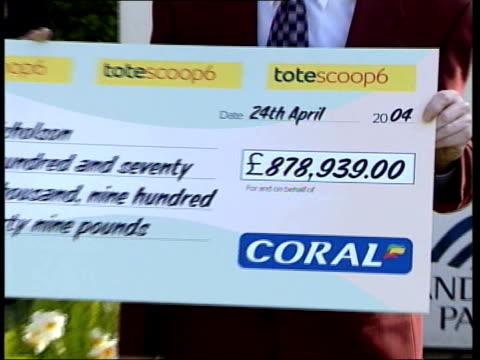 Man wins more than 870000 in accumulator bet ITN Ron Nicholson presented with cheque CS Cheque for 87800 pounds PULL GV Punters betting at tote stand...
